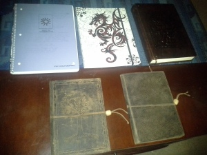 All of my writing journals so far.  From top left: TSOD book 1, TSOD book 2, TSOD book 3.  From bottom left, TSOD Bible, Chronicles of the Sentinels.